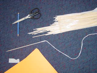 We taped a piece of string to the skewer so we could thread our ula. Can you see the scissors, skewers, paper and string?