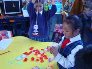 We are making patterns as we thread the flowers on to the string.