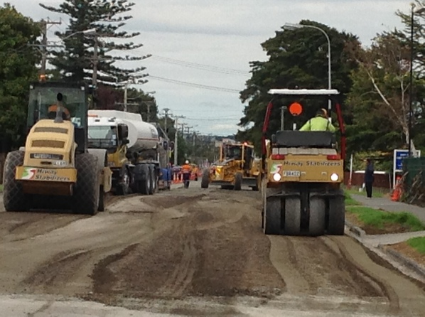 Lots of big, heavy machinery all working efficiently on a small stretch of road.