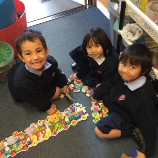 Micahel, Jayde and Justin are working together as they complete their puzzle,
