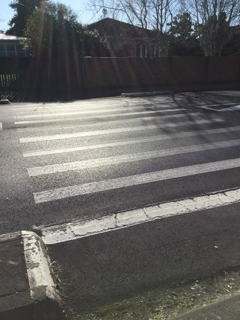 The pedestrian crossing is marked on the road with white paint
